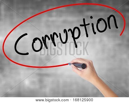 Woman Hand Writing Corruption With Black Marker Over Transparent Board