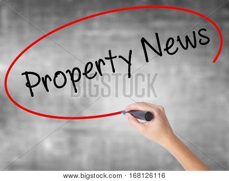 Woman Hand Writing Property News With Black Marker Over Transparent Board