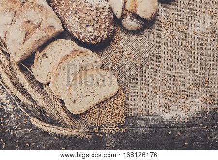 Plenty of sliced rye bread background. Bakery and grocery concept. Fresh, healthy sorts of rye and white loaves, sprinkled flour on sackcloth with copy space, top view