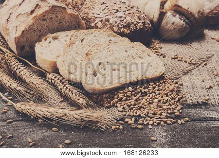 Plenty of sliced bread background. Bakery and grocery concept. Fresh, healthy sorts of rye and white loaves, sprinkled flour on sackcloth and rustic wood table, food closeup.