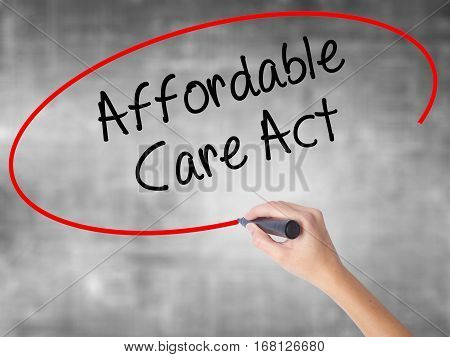 Woman Hand Writing Affordable Care Act With Black Marker Over Transparent Board