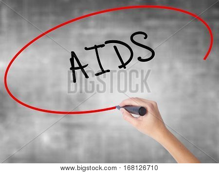 Woman Hand Writing Aids With Black Marker Over Transparent Board