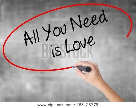 Woman Hand Writing All You Need Is Love With Black Marker Over Transparent Board
