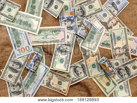 US Dollar bills and dollars bills rolled up on a burlap background