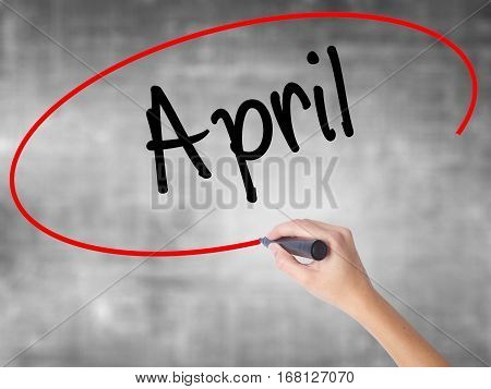 Woman Hand Writing  April  With Black Marker Over Transparent Board