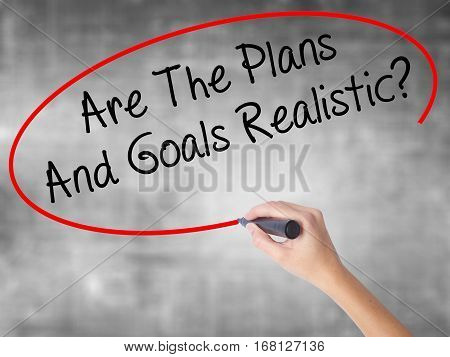 Woman Hand Writing Are The Plans And Goals Realistic? With Black Marker Over Transparent Board.