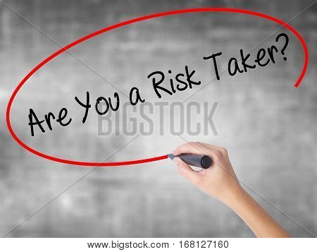 Woman Hand Writing Are You A Risk Taker? With Black Marker Over Transparent Board
