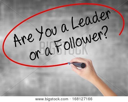 Woman Hand Writing Are You A Leader Or A Follower? With Black Marker Over Transparent Board