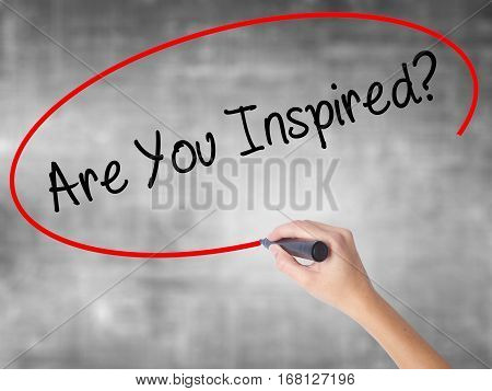 Woman Hand Writing Are You Inspired? With Black Marker Over Transparent Board