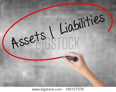 Woman Hand Writing Assets Liabilities With Black Marker Over Transparent Board