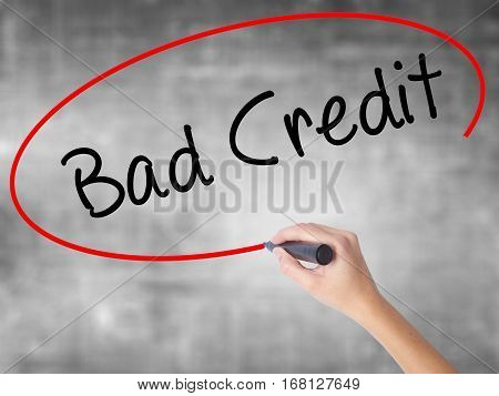 Woman Hand Writing Bad Credit With Black Marker Over Transparent Board