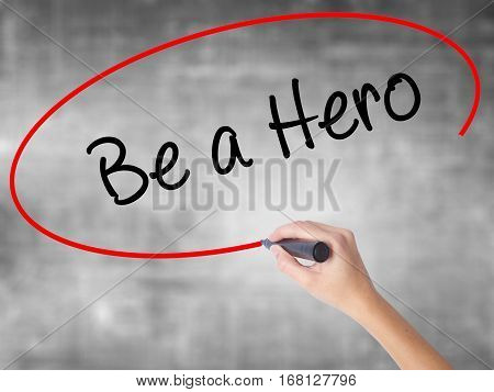 Woman Hand Writing Be A Hero  With Black Marker Over Transparent Board