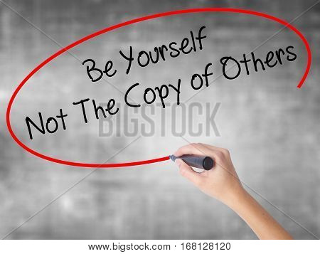 Woman Hand Writing Be Yourself Not The Copy Of Others With Black Marker Over Transparent Board