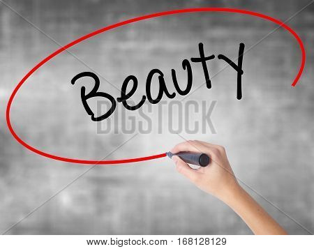 Woman Hand Writing Beauty  With Black Marker Over Transparent Board