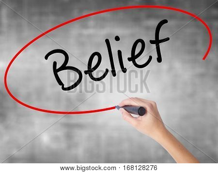 Woman Hand Writing Belief With Black Marker Over Transparent Board