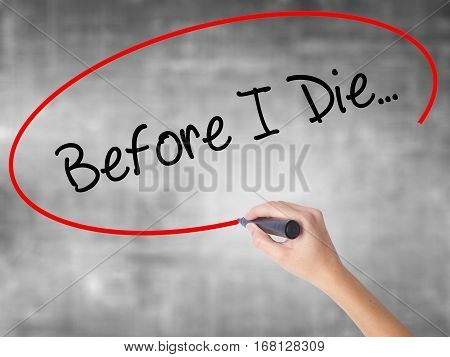 Woman Hand Writing Before I Die... With Black Marker Over Transparent Board.