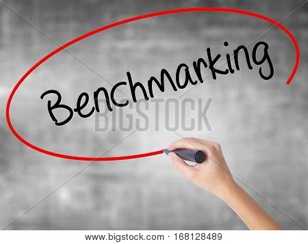 Woman Hand Writing Benchmarking  With Black Marker Over Transparent Board