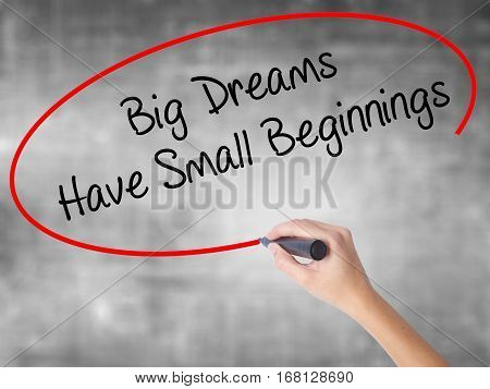 Woman Hand Writing Big Dreams Have Small Beginnings With Black Marker Over Transparent Board