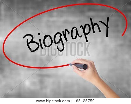Woman Hand Writing Biography  With Black Marker Over Transparent Board