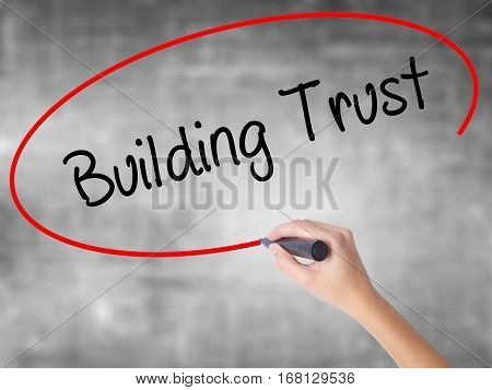 Woman Hand Writing Building Trust With Black Marker Over Transparent Board