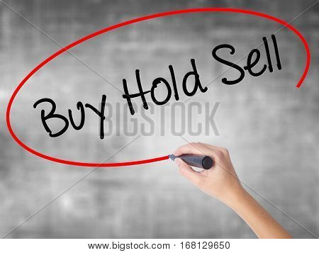 Woman Hand Writing  Buy Hold Sell With Black Marker Over Transparent Board