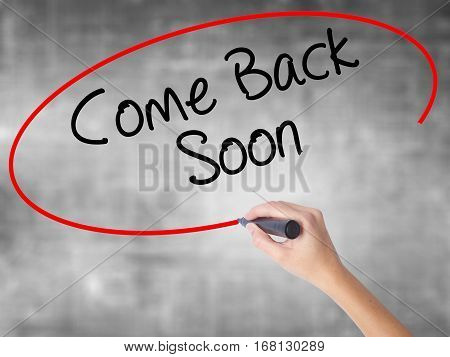 Woman Hand Writing Come Back Soon With Black Marker Over Transparent Board.