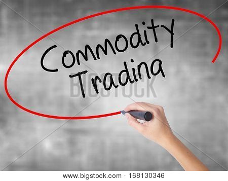 Woman Hand Writing Commodity Trading With Black Marker Over Transparent Board.