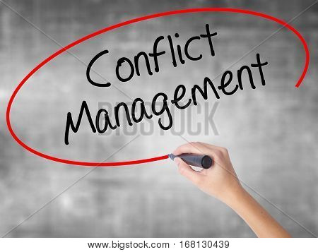Woman Hand Writing Conflict Management With Black Marker Over Transparent Board.