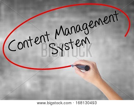 Woman Hand Writing Content Management System  With Black Marker Over Transparent Board