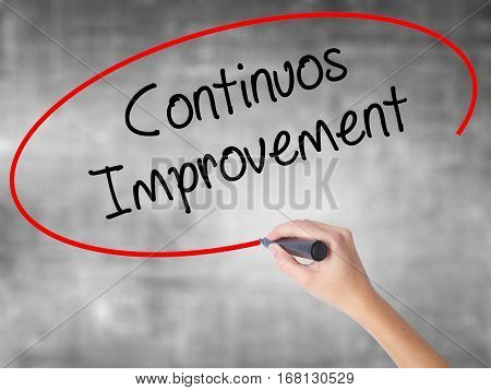 Woman Hand Writing Continuos Improvement With Black Marker Over Transparent Board