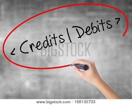 Woman Hand Writing Credits - Debits With Black Marker Over Transparent Board.