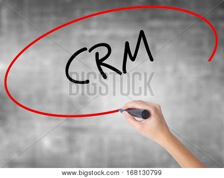 Woman Hand Writing Crm With Black Marker Over Transparent Board