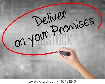 Woman Hand Writing Deliver On Your Promises With Black Marker Over Transparent Board