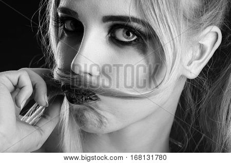 fun blond girl making fake mustache from her hair, monochrome image