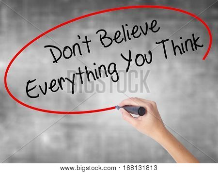 Woman Hand Writing Don't Believe Everything You Think With Black Marker Over Transparent Board.