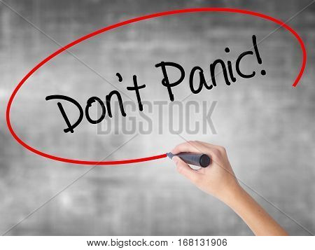 Woman Hand Writing Don't Panic! With Black Marker Over Transparent Board