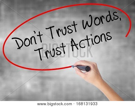 Woman Hand Writing Don't Trust Words, Trust Actions With Black Marker Over Transparent Board