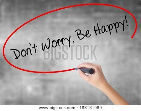 Woman Hand Writing Don't Worry, Be Happy! With Black Marker Over Transparent Board