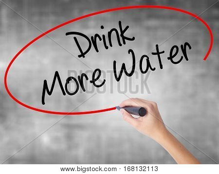 Woman Hand Writing Drink More Water With Black Marker Over Transparent Board