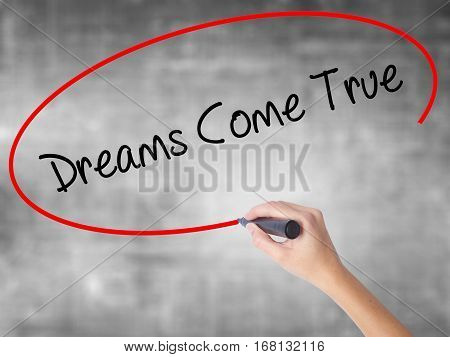 Woman Hand Writing Dreams Come True With Black Marker Over Transparent Board