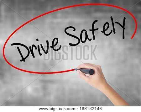 Woman Hand Writing  Drive Safely With Black Marker Over Transparent Board