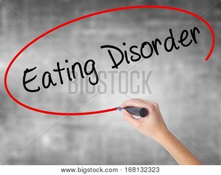 Woman Hand Writing Eating Disorder  With Black Marker Over Transparent Board