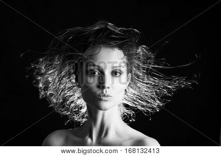 beautiful woman with flying wet hair on black background, monochrome
