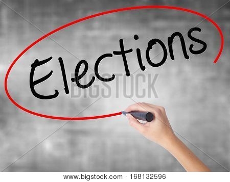 Woman Hand Writing Elections With Black Marker Over Transparent Board