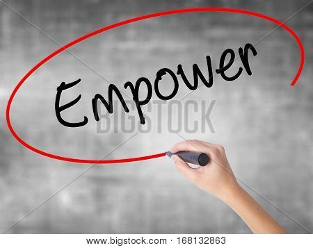 Woman Hand Writing Empower With Black Marker Over Transparent Board