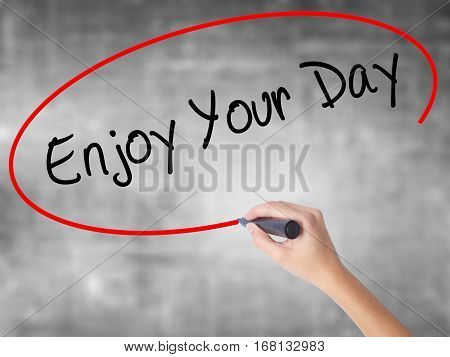 Woman Hand Writing Enjoy Your Day With Black Marker Over Transparent Board