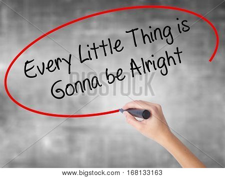 Woman Hand Writing Every Little Thing Is Gonna Be Alright With Black Marker Over Transparent Board