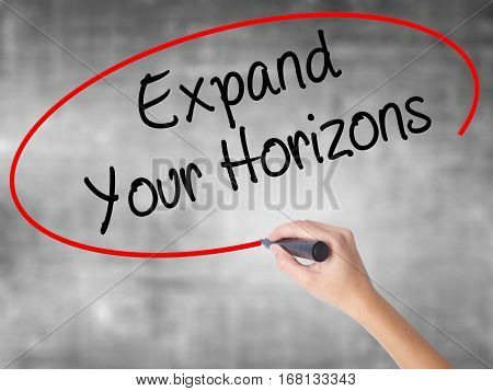 Woman Hand Writing  Expand Your Horizons  With Black Marker Over Transparent Board