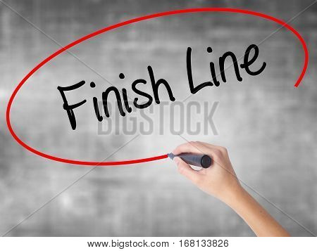 Woman Hand Writing Finish Line With Black Marker Over Transparent Board