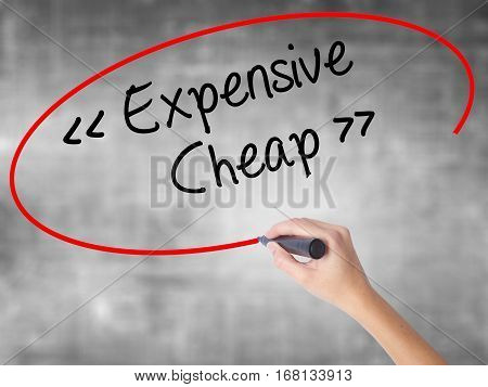 Woman Hand Writing Expensive - Cheap With Black Marker Over Transparent Board.